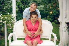 Pares novos felizes que esperam o bebê, mulher gravida com a barriga tocante do marido, sentando-se no sofá branco imagem de stock royalty free