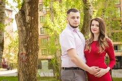 Pares novos felizes que esperam o bebê no parque do verão Imagem de Stock