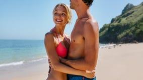 Pares novos felizes que estão junto na praia Fotografia de Stock