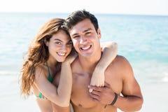 Pares novos felizes que estão na costa na praia Foto de Stock