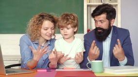 Pares novos felizes que est?o estando com seu filho na gradua??o Pouco menino de escola da criança em de primeiro grau Fam?lia filme