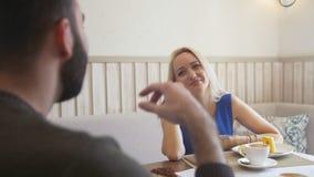 Pares novos felizes que falam ao apreciar sobremesas no café video estoque