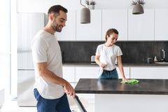 Pares novos felizes que fazem limpo geral na cozinha imagens de stock