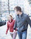 Pares novos felizes que guardam as mãos ao andar na rua da cidade imagem de stock royalty free