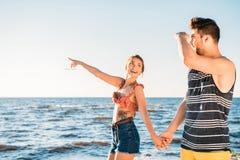 pares novos felizes que guardam as mãos e que olham afastado ao andar junto imagens de stock