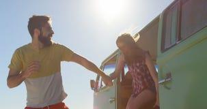 Pares novos felizes que guardam as mãos e que saem da camionete 4k vídeos de arquivo
