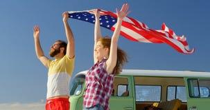 Pares novos felizes que guardam a bandeira americana na praia 4k filme