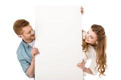 pares novos felizes que guardam o cartaz vazio e que olham o espaço da cópia fotografia de stock royalty free
