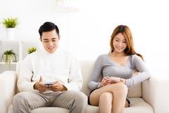 Pares novos felizes que guardam telefones celulares Fotografia de Stock Royalty Free