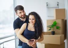 Pares novos felizes que movem-se na casa nova que desembala caixas fotos de stock