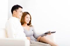 Pares novos felizes que olham a tevê na sala de visitas Fotografia de Stock Royalty Free