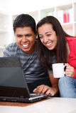 Pares novos felizes que olham um portátil Imagens de Stock