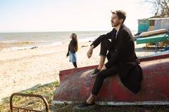 Pares novos felizes que passam o tempo na costa de mar na mola Imagens de Stock Royalty Free
