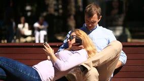 Pares novos felizes que relaxam no parque em um banco, menina que inclina-se no regaço de seu noivo e que olha o telefone video estoque