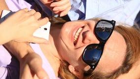 Pares novos felizes que relaxam no parque em um banco, menina que inclina-se no regaço de seu noivo e que olha o telefone filme