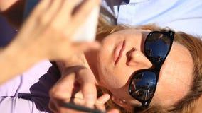 Pares novos felizes que relaxam no parque em um banco, menina que inclina-se no regaço de seu noivo e que olha o telefone vídeos de arquivo
