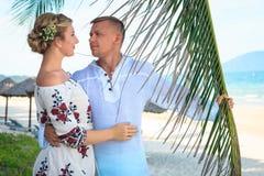 Pares novos felizes que riem e que abraçam na praia fotos de stock royalty free