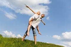 Pares novos felizes que saltam acima do prado verde Imagem de Stock