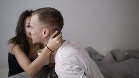 Pares novos felizes que sentam-se na cama e no café bebendo na manhã Sorrindo, menina moreno feliz que beija a filme