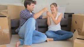 Pares novos felizes que sentam-se no sofá em no sua casa e cheering novos vídeos de arquivo