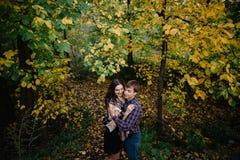 Pares novos felizes que sorriem e que riem na floresta do outono foto de stock
