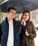 Pares novos felizes que sorriem sob o guarda-chuva Fotos de Stock Royalty Free