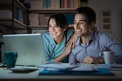 Pares novos felizes que surfam a Web em casa Foto de Stock