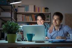 Pares novos felizes que surfam a Web em casa imagens de stock royalty free