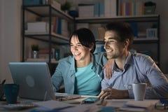 Pares novos felizes que surfam a Web em casa Fotografia de Stock Royalty Free