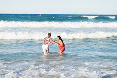 Pares novos felizes que têm o divertimento, o homem e a mulher no mar em uma praia Foto de Stock Royalty Free