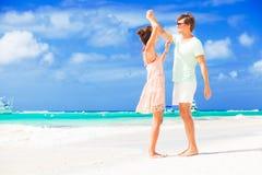 Pares novos felizes que têm o divertimento pela praia Fotografia de Stock