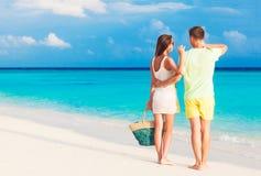 Pares novos felizes que têm o divertimento pela praia Imagem de Stock