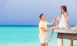 Pares novos felizes que têm o divertimento pela praia Foto de Stock