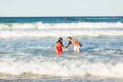 Pares novos felizes que têm o divertimento, o homem e a mulher no mar em uma praia Fotos de Stock Royalty Free