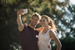 Pares novos felizes que tomam o selfie no dia ensolarado na exploração agrícola imagens de stock