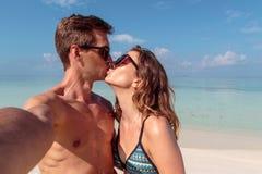 Pares novos felizes que tomam um selfie, ?gua azul clara como o fundo Menina que beija seu noivo fotografia de stock