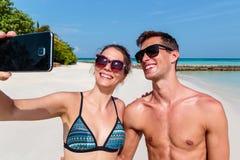 Pares novos felizes que tomam um selfie Ilha tropical como o fundo fotografia de stock royalty free