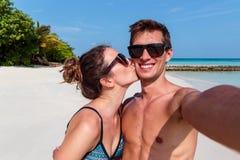 Pares novos felizes que tomam um selfie, uma ilha tropical e uma ?gua azul clara como o fundo Menina que beija seu noivo foto de stock