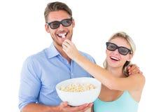 Pares novos felizes que vestem os vidros 3d que comem a pipoca Fotografia de Stock Royalty Free