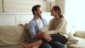 Pares novos felizes românticos que tocam nas testas que riem o afago no sofá vídeos de arquivo