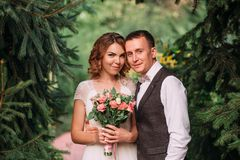 Pares novos felizes, uma noiva loura no vestido de casamento surpreendente branco leve, guardando o ramalhete de flores cor-de-ro foto de stock royalty free