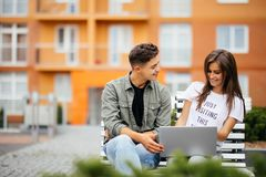 Pares novos felizes usando o laptop que senta-se em um banco na cidade exterior Dois amantes que têm o divertimento que passa o t Foto de Stock Royalty Free