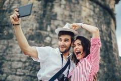 Pares novos felizes usando uma tabuleta digital junto fotografia de stock