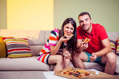 Pares novos funky que comem a pizza em um sofá Imagem de Stock Royalty Free