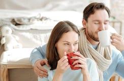 Pares novos inspirados que relaxam em casa junto Imagem de Stock