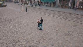 Pares novos junto no centro da rua Homem com um ramalhete das flores Tiro do ar video estoque