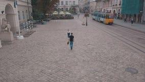 Pares novos junto no centro da rua Homem com um ramalhete das flores Tiro do ar vídeos de arquivo