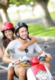 Pares novos livres no 'trotinette' em férias de verão Imagens de Stock