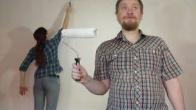 Pares novos loucos que fazem reparos na sala, pintando a parede com rolos filme