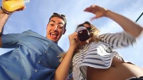 Pares novos loucos que olham para baixo na câmera, em cocktail bebendo e no riso filme